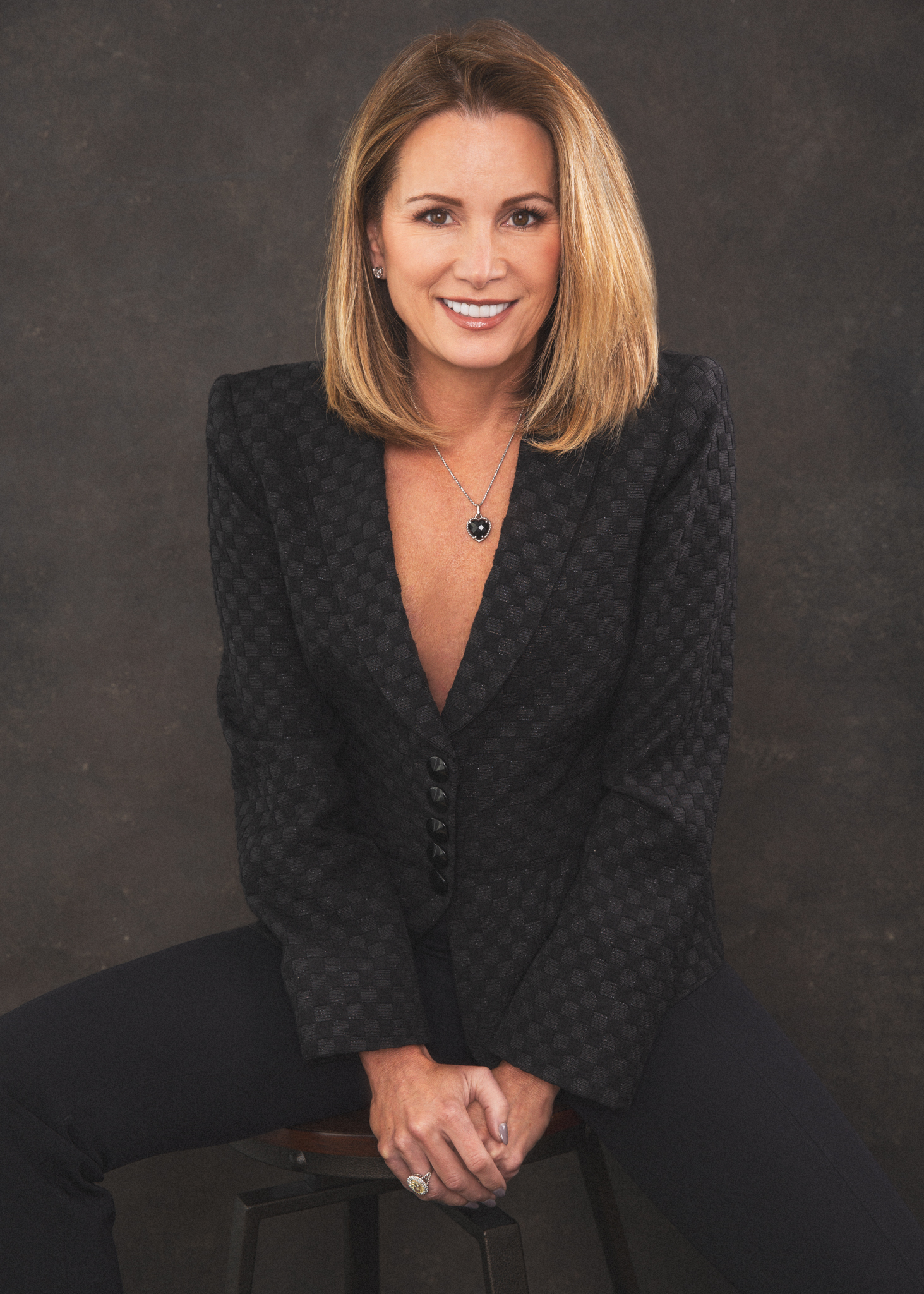 Blonde business woman in a suit seated on a stool in front of a dark background.