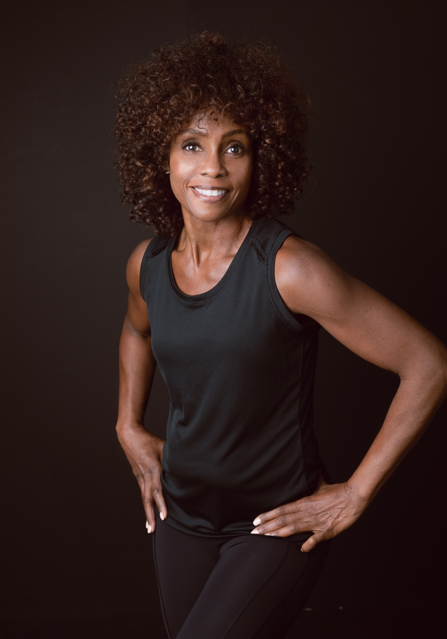 Black woman athlete standing in front of a brown background.