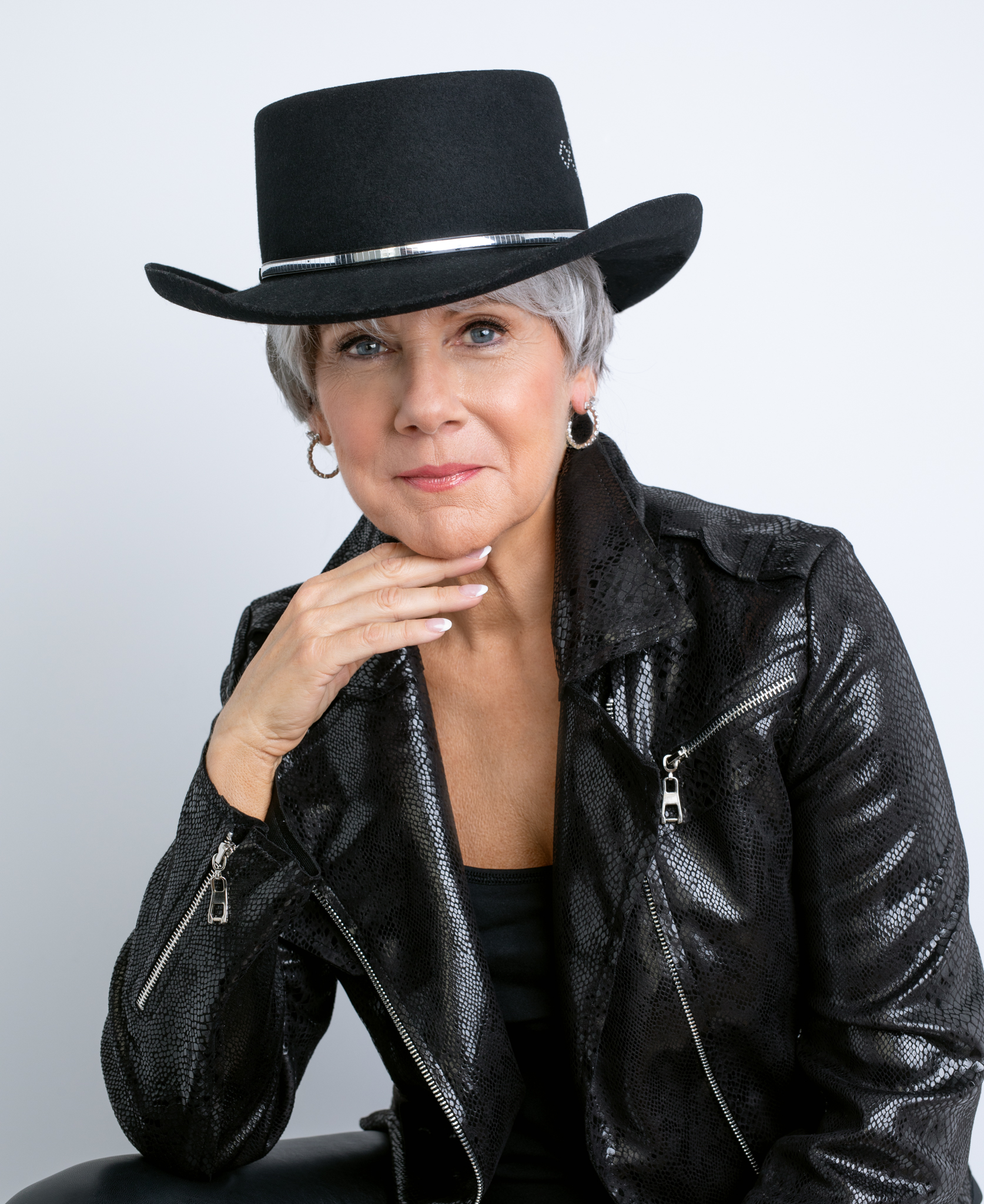 Gray haired woman in black hat and black leather jacket.