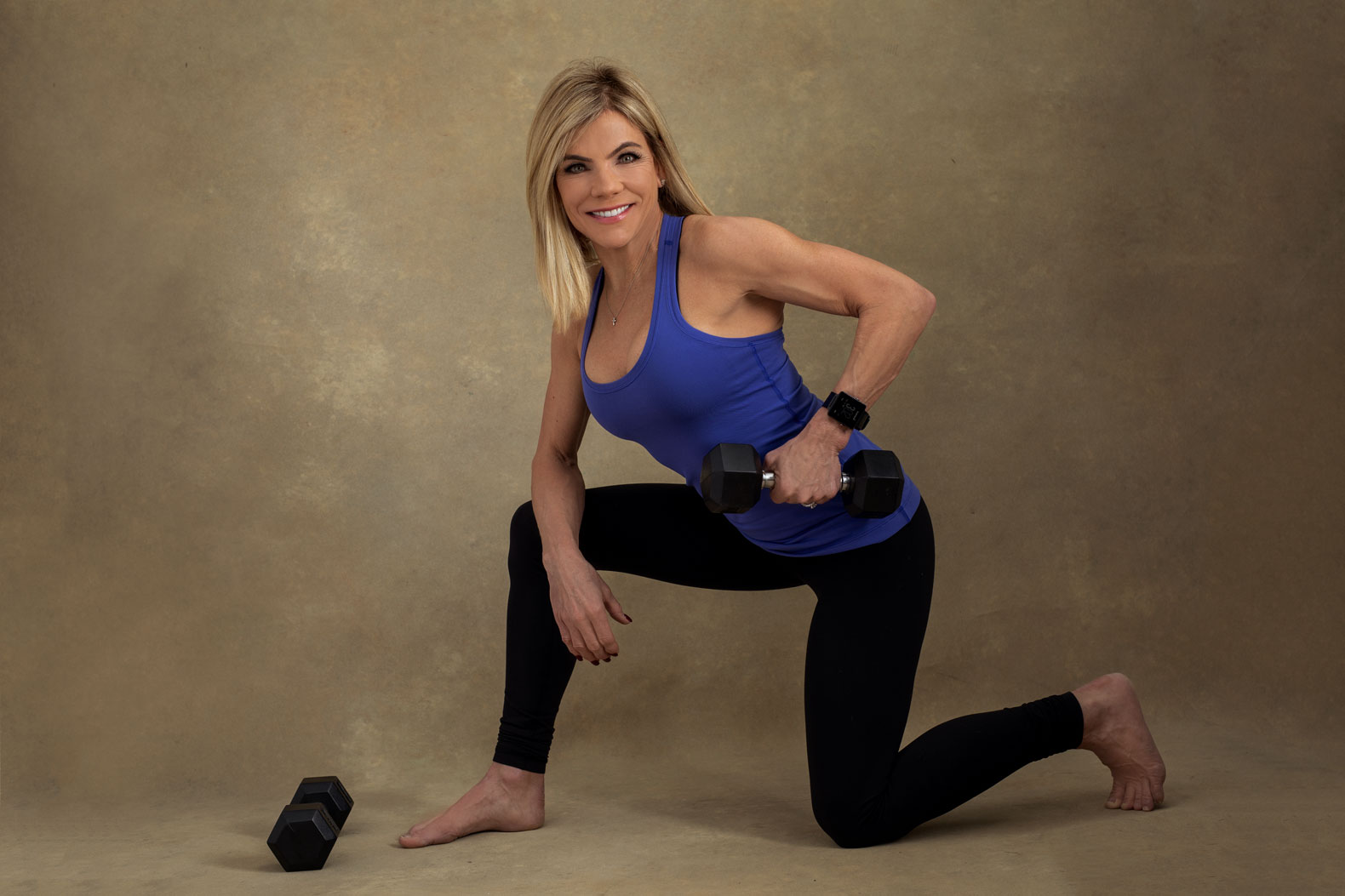 Muscular woman kneeling and lifting weights.