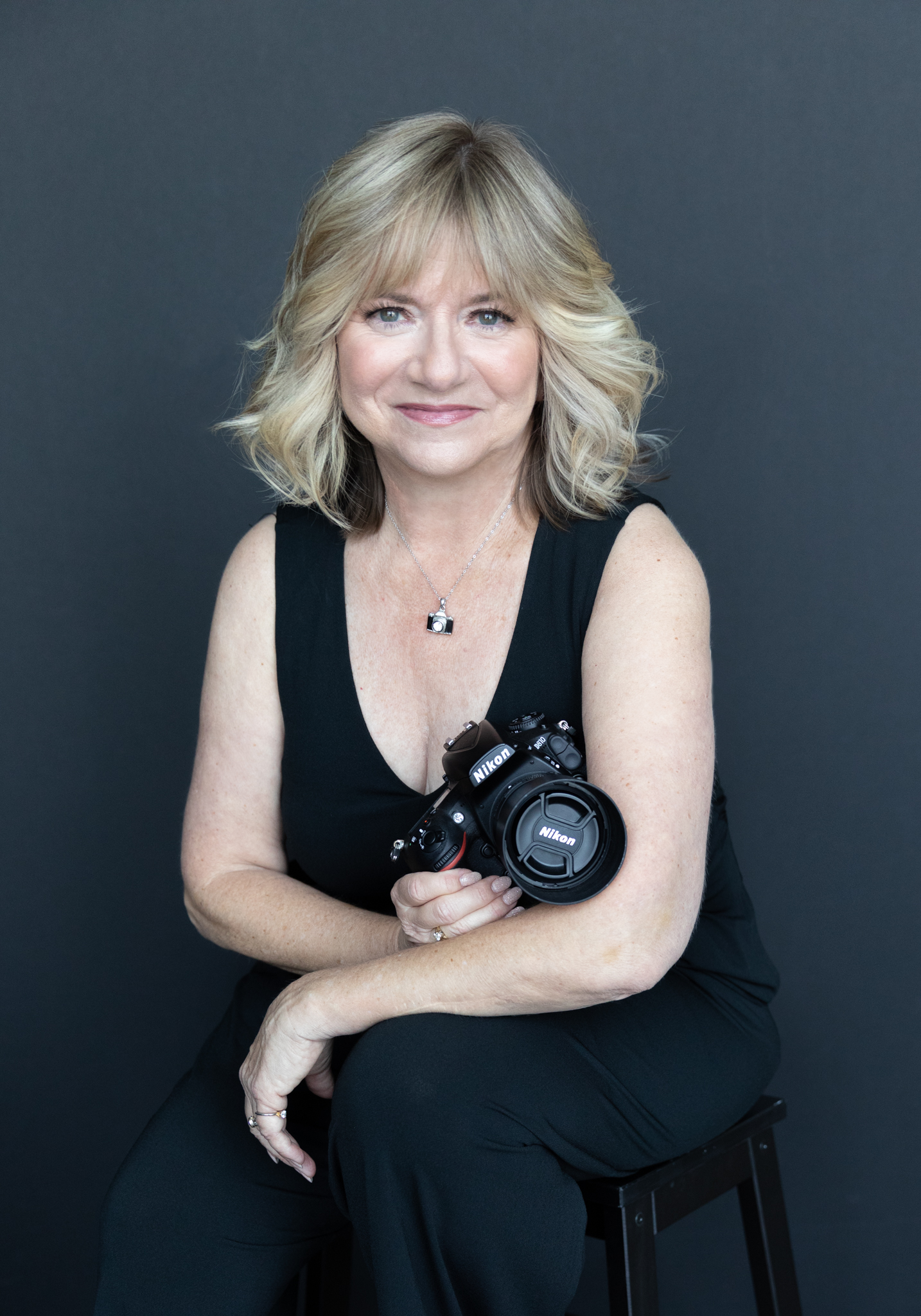 Woman photographer seated wearing black and holding a camera.