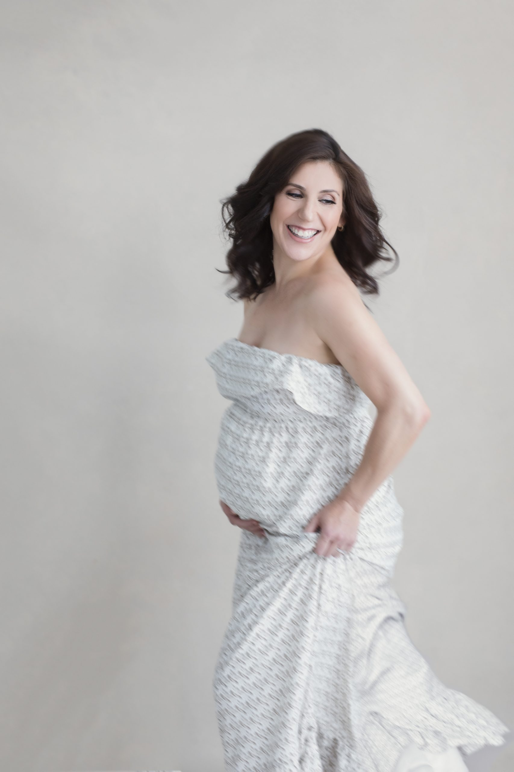 Pregnant woman with brown hair dancing and smiling.