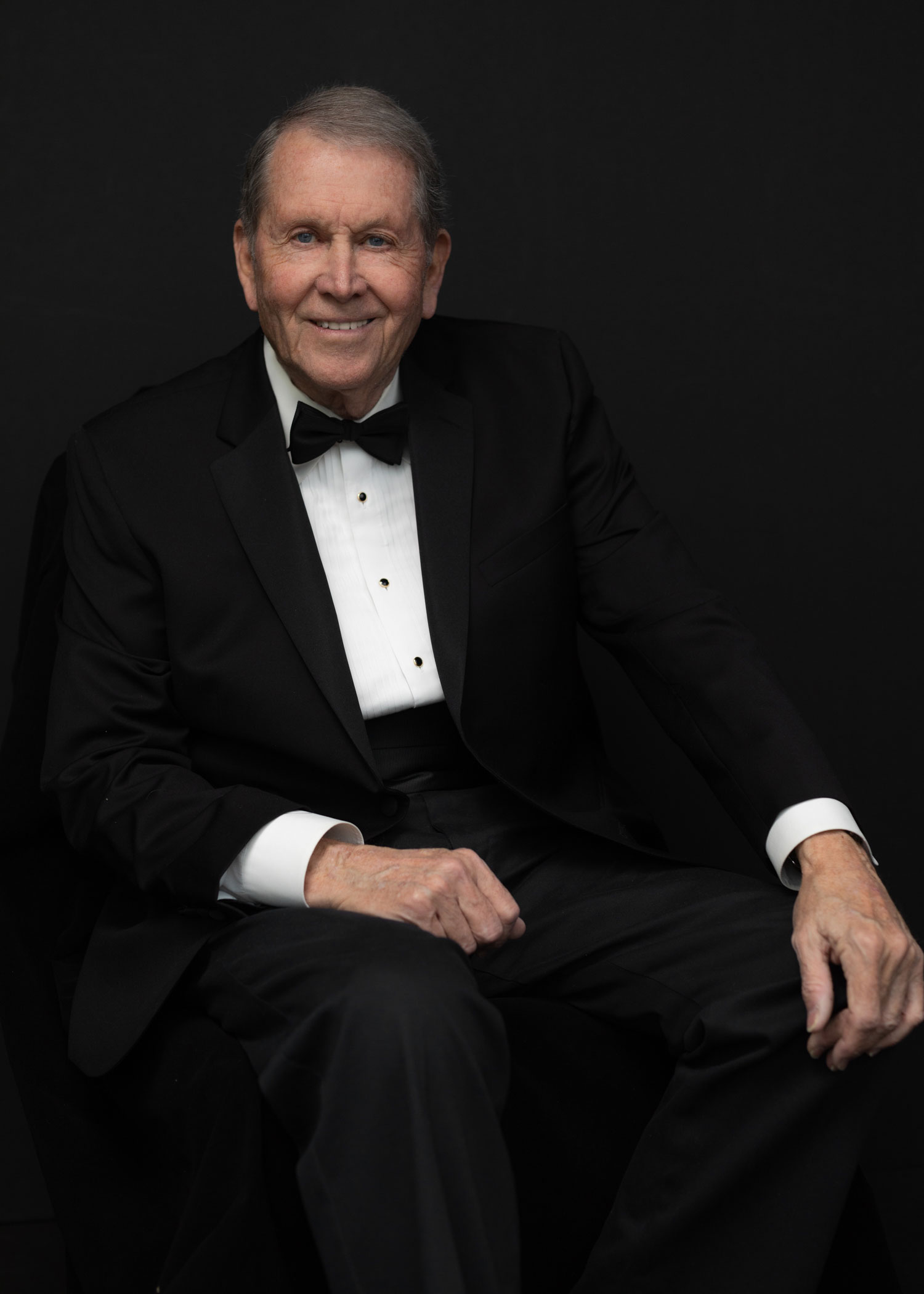 Handsome older gentleman smiling and seated  formal attire.