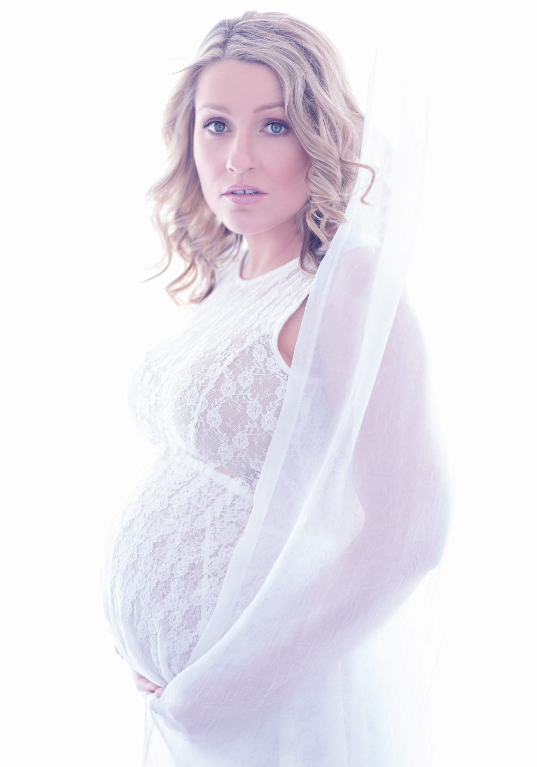 High Key beautiful blonde pregnant woman behind a sheer curtain in a lace dress!